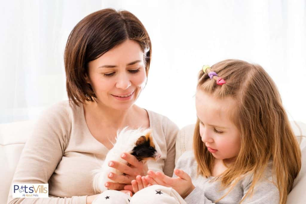 a women with her kid trying to gain trust of guinea pig